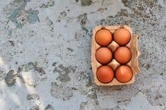 Frische Eier im braunen Papierkasten auf einem rustikalen Hintergrund Lizenzfreies Stockfoto