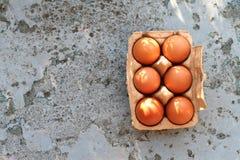 Frische Eier im braunen Papierkasten auf einem rustikalen Hintergrund Stockfotografie