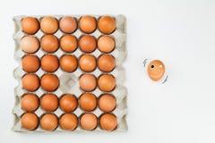Frische Eier im Papierbehälter mit einem lächelnden Ei aus Behälter auf weißem Hintergrund heraus Stockbilder
