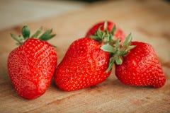 Frische Erdbeere auf einem dunklen hölzernen Hintergrund, Abschluss oben der großen Erdbeere auf Holz Lizenzfreies Stockbild