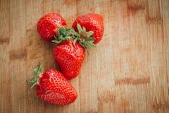 Frische Erdbeere auf einem dunklen hölzernen Hintergrund, Abschluss oben der großen Erdbeere auf Holz Stockfoto