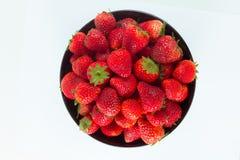 Frische Erdbeere in einer schwarzen Schale und in einem weißen Hintergrund Stockbilder