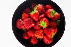 Frische Erdbeere in einer schwarzen Schale und in einem weißen Hintergrund Lizenzfreie Stockfotos