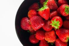 Frische Erdbeere in einer schwarzen Schale und in einem weißen Hintergrund Stockbild