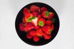 Frische Erdbeere in einer schwarzen Schale und in einem weißen Hintergrund Lizenzfreie Stockbilder