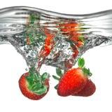Frische Erdbeere fiel in Wasser mit Spritzen Stockbilder
