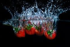 Frische Erdbeere fiel in Wasser mit Spritzen auf schwarzem backgro Stockfotografie