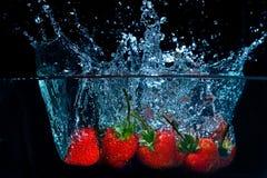 Frische Erdbeere fiel in Wasser mit Spritzen auf schwarzem backgro Stockbilder