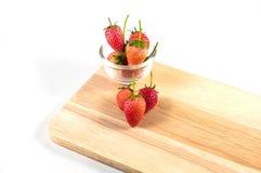 Frische Erdbeeren auf hölzernem und im Glas auf weißem Hintergrund Lizenzfreies Stockfoto
