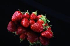 Frische Erdbeeren auf reflektierendem schwarzem Hintergrund Stockfoto