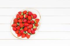 Frische Erdbeeren in der Platte auf weißem Holztisch Beschneidungspfad eingeschlossen Lizenzfreies Stockfoto