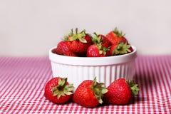 Frische Erdbeeren in der weißen Schüssel auf roter Gingham-Tischdecke Lizenzfreies Stockbild