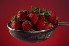 Frische Erdbeeren in einem Sieb auf einem roten Hintergrund Stockfotografie