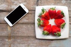 Frische Erdbeeren in einem Teller und in einem Telefon auf Holztisch Lizenzfreies Stockfoto