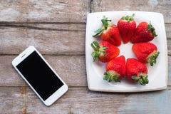 Frische Erdbeeren in einem Teller und in einem Telefon auf Holztisch Lizenzfreie Stockbilder