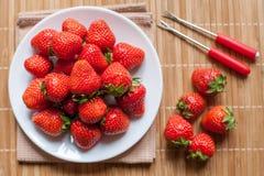 Frische Erdbeeren in einer Schüssel auf Holztisch Stockfotografie