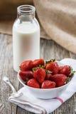 Frische Erdbeeren mit einer Flasche Milch Stockbilder