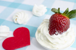 Frische Erdbeeren mit Sahne auf einer blauen Tischdecke und einer Meringe Lizenzfreie Stockfotos