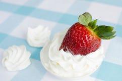 Frische Erdbeeren mit Sahne auf einer blauen Tischdecke und einer Meringe Stockbilder