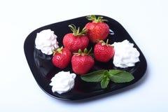 Frische Erdbeeren mit Schlagsahne und tadellosen Blättern auf einem Schwarzblech Selektiver Fokus Stockbild