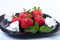 Frische Erdbeeren mit Schlagsahne und tadellosen Blättern auf einem Schwarzblech Selektiver Fokus Stockfoto