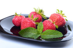 Frische Erdbeeren und tadellose Blätter auf Schwarzblech Selektiver Fokus Stockfotografie