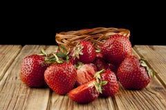 Frische Erdbeerfrucht auf einem Holztisch lokalisiert auf einem Schwarzen Stockbild