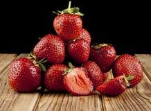 Frische Erdbeerfrucht auf einem Holztisch lokalisiert auf einem Schwarzen Lizenzfreie Stockfotografie