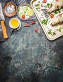 Frische Fische auf dem Kochen der Wanne mit Bestandteilen, Öl und Gewürzen auf rustikalem Hintergrund, Draufsicht Gesunde Nahrung Stockfotos