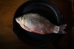 Frische Fische in einer Bratpfanne auf einem schwarzen Hintergrund Stockfotos