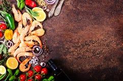 Frische Fische, Garnelen mit Kräutern, Gewürze und Gemüse auf dunklem Weinlesehintergrund Gesundes Lebensmittel, Diät oder kochen Stockfoto
