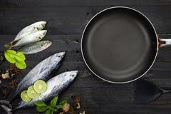 Frische Fische und schwarze Bratpfanne auf Hintergrund des dunklen Schwarzen, Fisch w Stockfotos