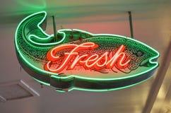 Frische Fische unterzeichnen mit orange und grünem Neonentwurf Lizenzfreie Stockbilder