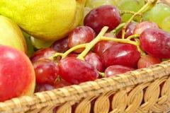 Frische Früchte auf einem Strohtopf. Lizenzfreies Stockbild