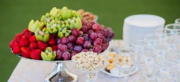 Frische Früchte auf Platte Erdbeeren, Kiwi, Trauben und Acajounüsse auf Verpflegungsbankettisch Lizenzfreie Stockbilder