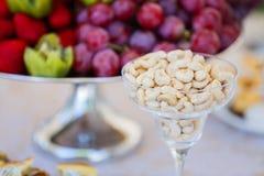 Frische Früchte auf Platte Erdbeeren, Kiwi, Trauben und Acajounüsse auf Verpflegungsbankettisch Stockfotos