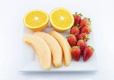 Frische Früchte in der Platte auf weißem Hintergrund Stockfotografie