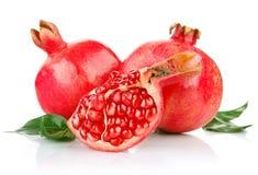 Frische Früchte des Granatapfels mit Schnitt- und Grünblättern Lizenzfreies Stockfoto