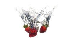 Frische Früchte fielen in Wasser mit Spritzen Lizenzfreies Stockfoto