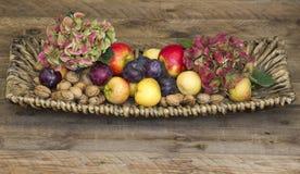 Frische Früchte und Blumen in einem Korb stockfoto