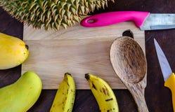Frische Früchte und Messer auf hackendem Brett stockfoto