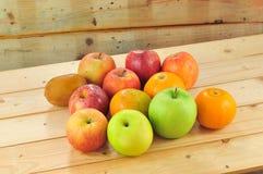 Frische Früchte wie Orangen, rote Äpfel auf dem Tisch mit hölzernem Hintergrund Stockbild