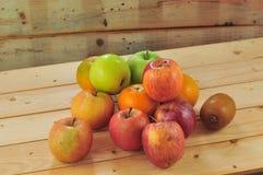 Frische Früchte wie Orangen, rote Äpfel auf dem Tisch mit hölzernem Hintergrund stockfotografie