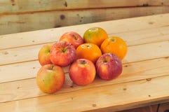 Frische Früchte wie Orangen, rote Äpfel auf dem Tisch mit hölzernem Hintergrund Lizenzfreies Stockbild