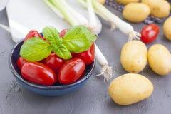 Frische Frühlingszwiebeln, junge Kartoffeln, Kirschtomaten und grüner Basilikum gesundes Lebensmittel und Vitamine Sommersaisonge stockfoto