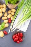 Frische Frühlingszwiebeln, junge Kartoffeln, Kirschtomaten und grüner Basilikum gesundes Lebensmittel und Vitamine Sommersaisonge lizenzfreie stockfotos