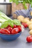 Frische Frühlingszwiebeln, junge Kartoffeln, Kirschtomaten und grüner Basilikum gesundes Lebensmittel und Vitamine Vorbereitung d stockbild