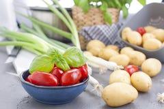 Frische Frühlingszwiebeln, junge Kartoffeln, Kirschtomaten und grüner Basilikum gesundes Lebensmittel und Vitamine Vorbereitung d stockfotografie