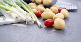 Frische Frühlingszwiebeln, junge Kartoffeln und Kirschtomaten gesundes Lebensmittel und Vitamine Sommersaisongemüse Kopieren Sie  lizenzfreies stockbild