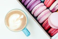 Frische französische macaron Plätzchen und blaue Schale Cappuccino auf weißer Tabelle Stockbilder
